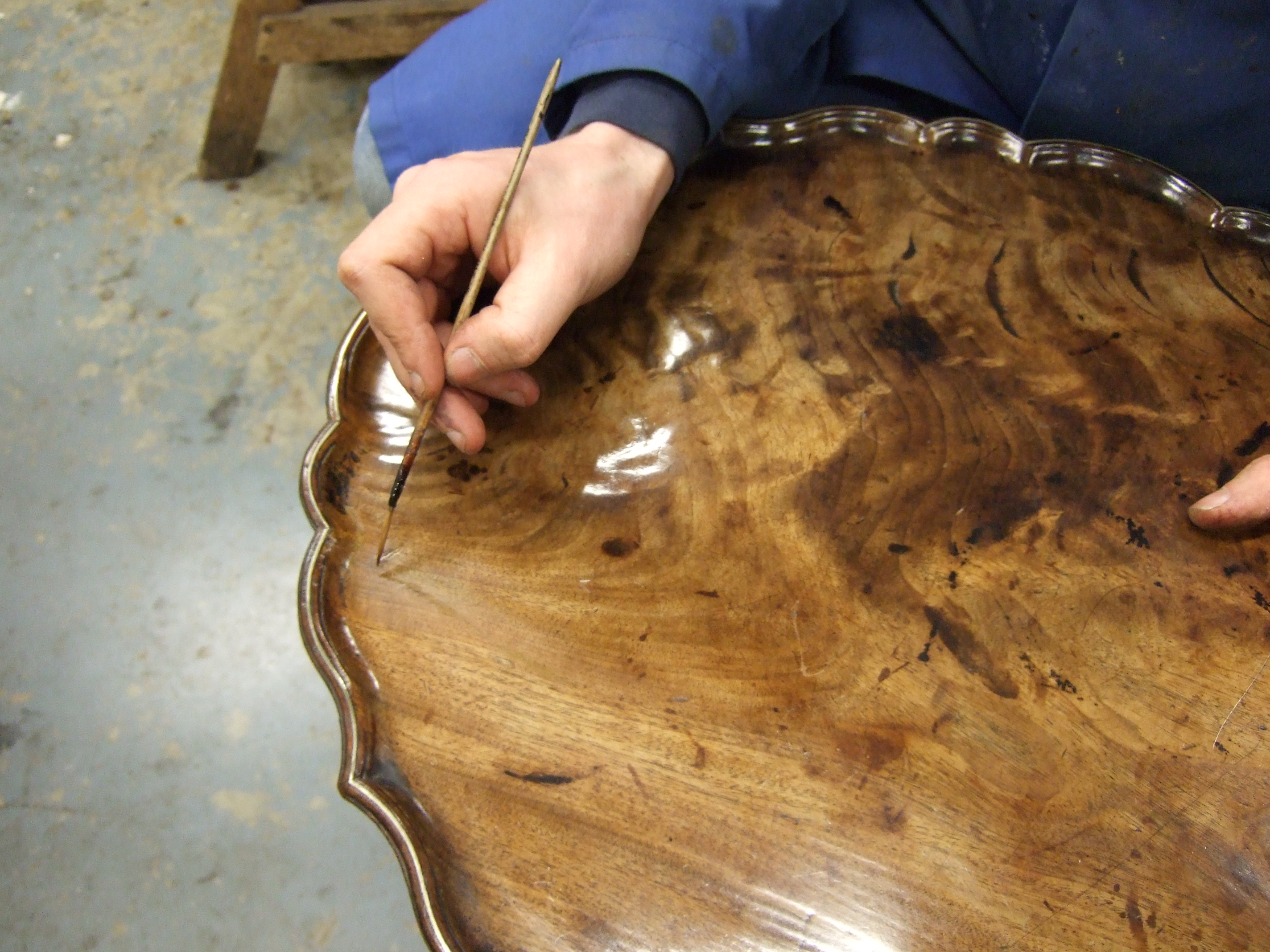 A George II Pie Crust Tripod Table, Circa 1750. Colouring a repaired split to the top using a fine pencil brush.